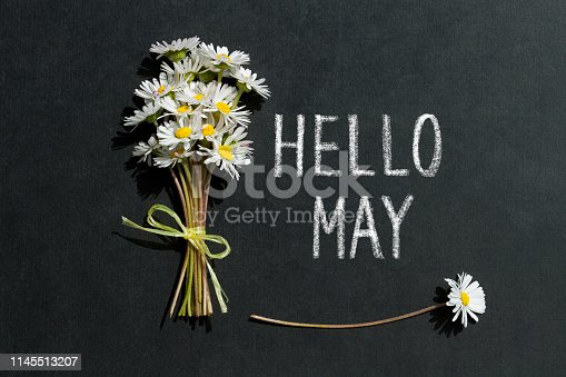 Daisies and text Hello May on blackboard