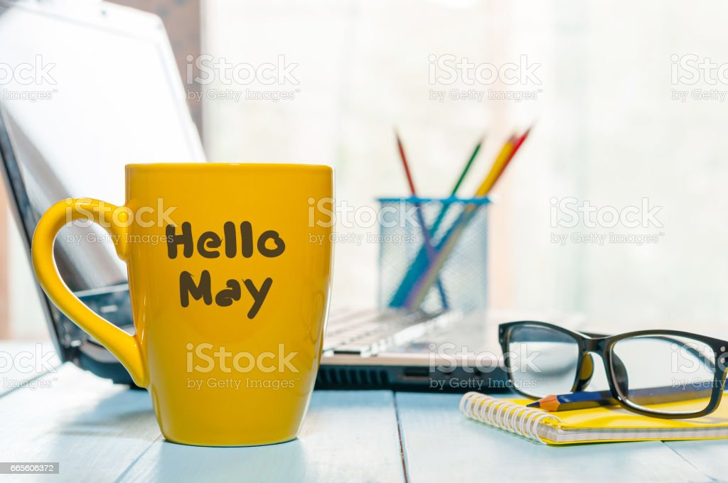 Hello MAY - text on yellow coffee cup at business office background, workplace with laptop and glasses. Spring time, empty space for text stock photo