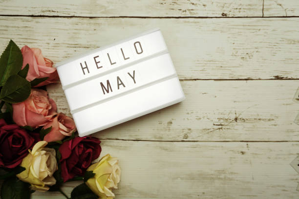 Hello May Word on Light box with roses flower bouquet on wooden background stock photo