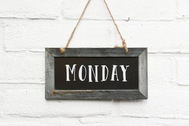 Hello monday motivation for a new week text on hanging board white brick outdoor wall stock photo