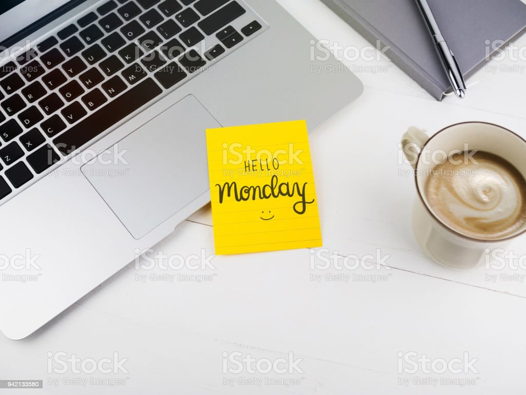 Hello Monday text with smiley face on sticky note on desk stock photo