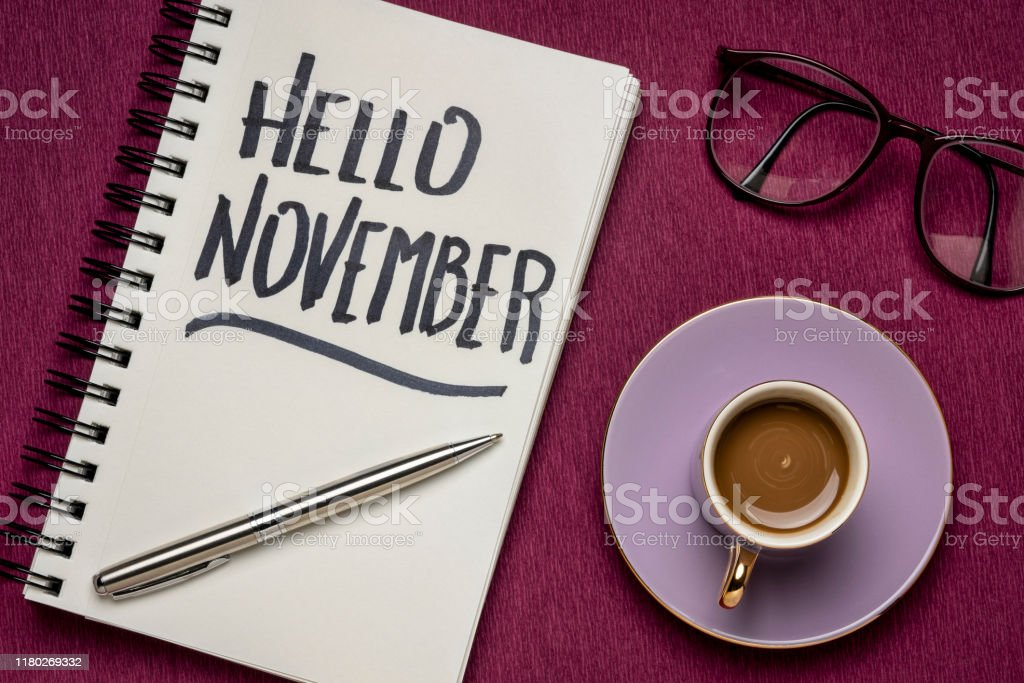 Hello November - handwriting in a notebook with a cup of coffee,...