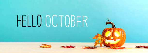Hello October message with pumpkin on a table Hello October messag with pumpkin with leaves on a blue background october stock pictures, royalty-free photos & images