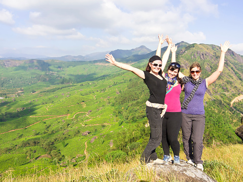 Hello from three beautiful young woman flying on top of mountain above Munnar Tea fields on around 1600 m above sea level in the Western Ghats range of mountains in the southwestern state of Kerala, India. It is part of UNESCO World Heritage Site as one of the eight hottest places of biological diversity in the world.