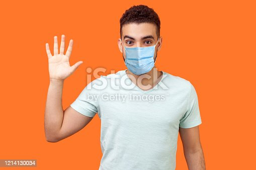 Hello! Portrait of friendly glad handsome man with medical mask in casual white t-shirt showing hi gesture with waving hand and smiling sincerely. indoor studio shot isolated on orange background