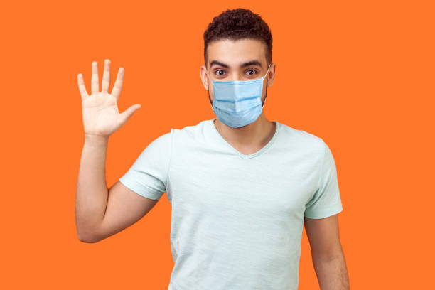 Hello! Portrait of friendly glad handsome man with medical mask in casual white t-shirt showing hi gesture with waving hand and smiling sincerely. stock photo
