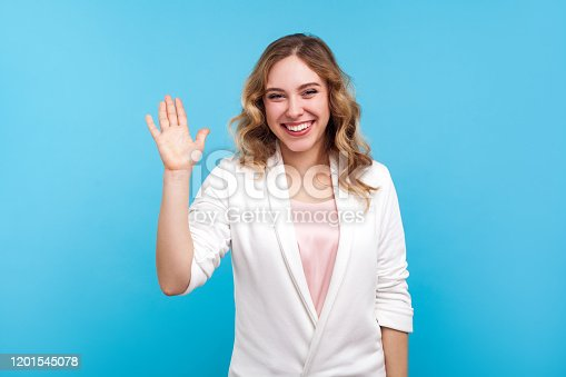 Hello! Portrait of friendly kind cheerful girl with wavy hair in white jacket waving hand saying hi welcome, smiling with hospitable sociable expression. indoor studio shot isolated on blue background