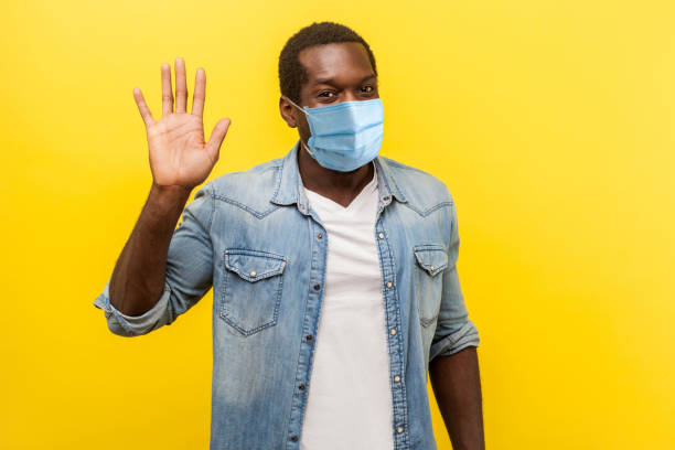 Hello! Portrait of positive handsome man with medical mask with rolled up sleeves smiling friendly and waving hand saying hi, welcoming gesture. stock photo