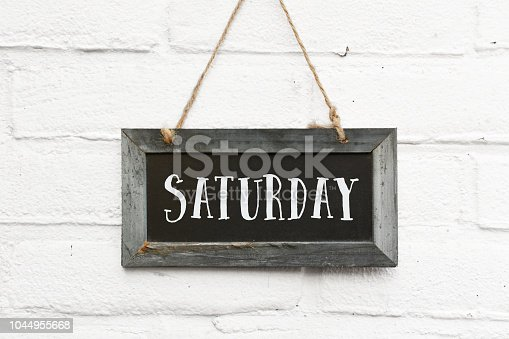 Hello saturday text on hanging board white brick outdoor wall