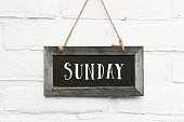 istock Hello saturday weekend text on wooden blackboard against white brick outdoor wall 1044956134