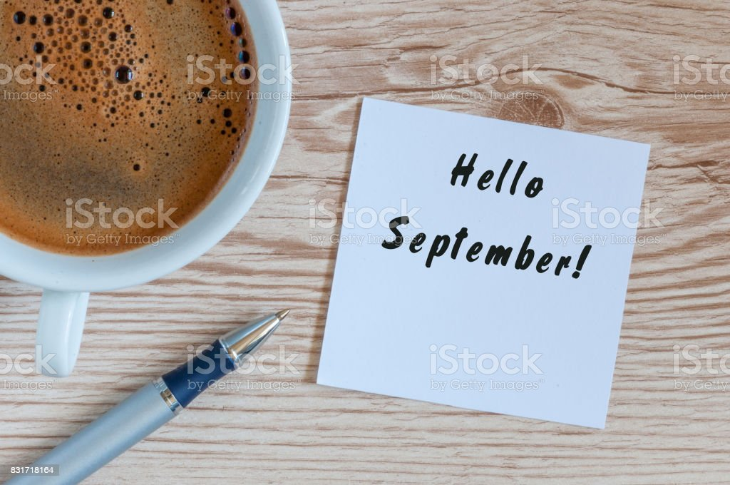 Hello September wrote at paper sticker with coffee and pen on wooden background stock photo