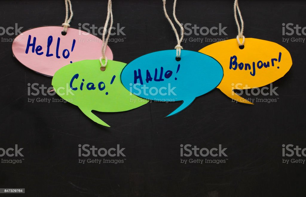 Hello / Speaking learning foreign languages. colorful speech bubbles hanging from a cord on blackboard background stock photo