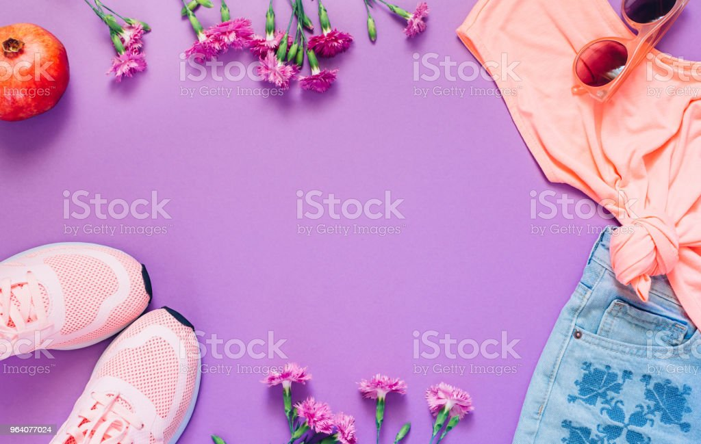 Hello spring or summer concept. Female clothes, flowers and pomegranate layout on purple background. Flat lay. Top view - Royalty-free Backgrounds Stock Photo