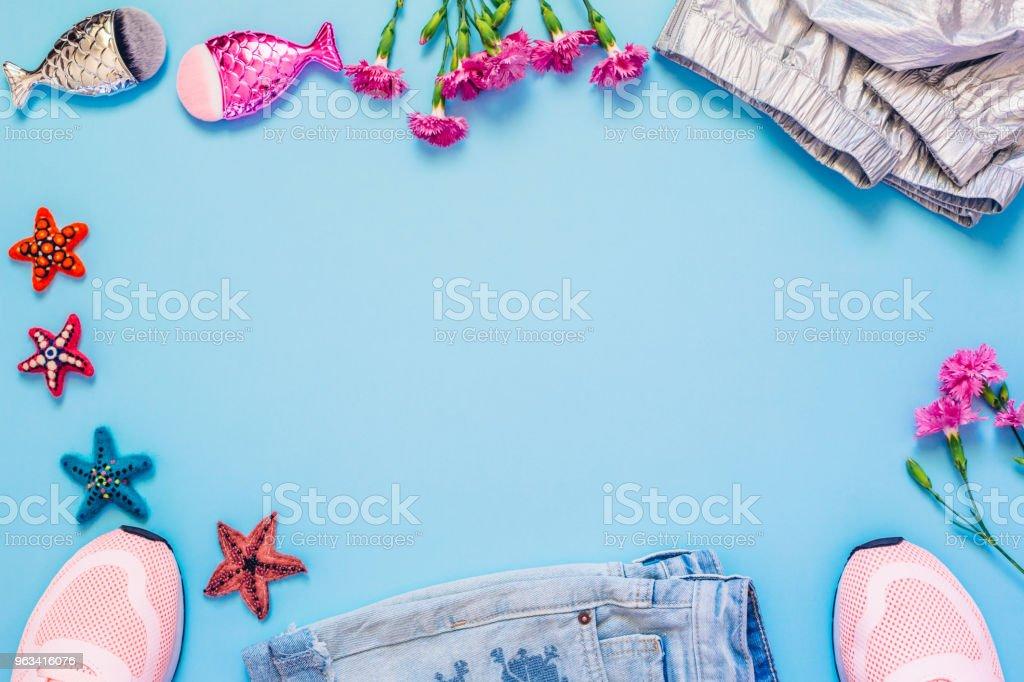 Bonjour le concept de printemps ou d'été. Vêtements féminins, de fleurs et de mise en page de pinceaux de maquillage sur fond bleu ciel. Poser de plat. Vue de dessus. - Photo de Abri de plage libre de droits