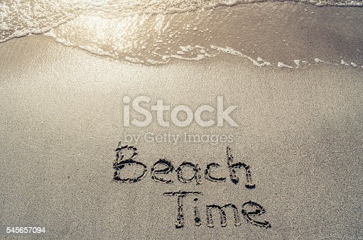 500536143istockphoto Hello summer handwritten on beach sand. Water sea background. 545657094