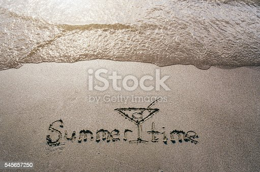 500536143istockphoto Hello summer handwritten on beach sand. Water sea background. 545657250