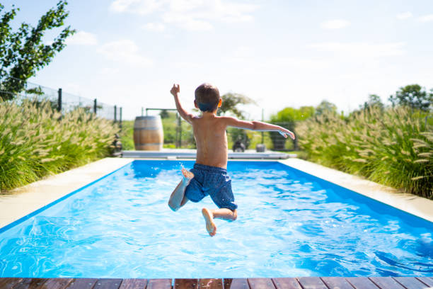 hello summer holidays - boy jumping in swimming pool rear view of 4 year old boy jumping into private pool on sunny vacation day - boy is unrecognizable so can be used anonymous summer fun series mid air stock pictures, royalty-free photos & images