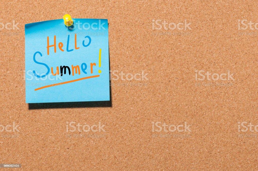 Hej sommar - text på lilla blå papper fäst för att kork ombord bakgrund. Första sommardag, kalender koncept. Med kopia utrymme för text - Royaltyfri Anteckningsblock Bildbanksbilder
