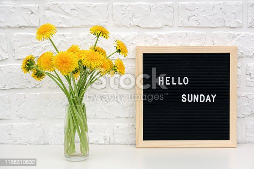 Hello Sunday words on black letter board and bouquet of yellow dandelions flowers on table against white brick wall. Concept Happy Monday. Template for postcard.