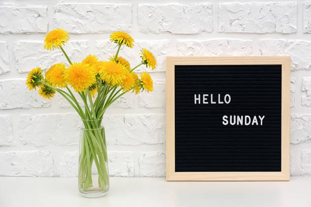黒い文字ボード上のこんにちは日曜日の言葉と白いレンガの壁に対してテーブルの上に黄色のタンポポの花の花束。コンセプトハッピーマンデー。はがき用テンプレート - 週末の予定 ストックフォトと画像