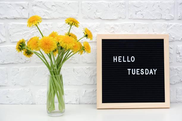 hallo dienstag worte auf schwarzem brieftafel und strauß von gelben löwenzahn blumen auf dem tisch gegen weiße ziegelwand. konzept happy monday. vorlage für postkarte - glückliche montagszitate stock-fotos und bilder