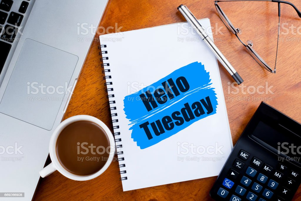 'Hello Tuesday' words on notebook with a cup of coffee, pen, calculator, spectacles, and a a laptop - greeting, sign and business concept stock photo