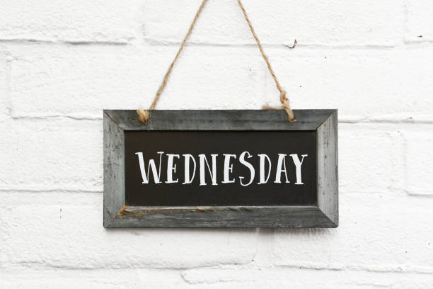 Hello wednesday quote on sign text board against white brick outdoor wall stock photo