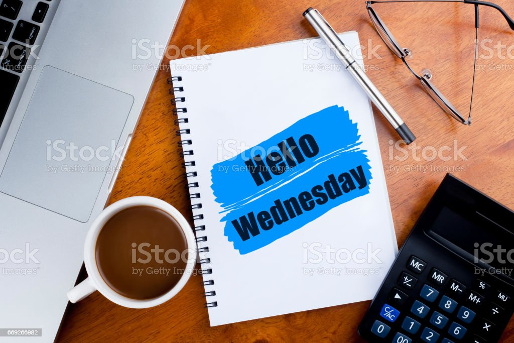 'Hello Wednesday' words on notebook with a cup of coffee, pen, calculator, spectacles, and a a laptop - greeting, sign and business concept stock photo