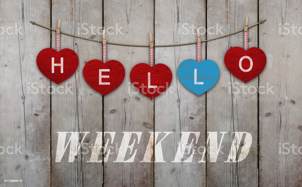 Hallo weekend geschreven op de rode en blauwe houten hartjes, op de achtergrond van opknoping gebruikt steiger hout foto