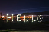 A light painting image with the word 'hello' written with light from a lantern.