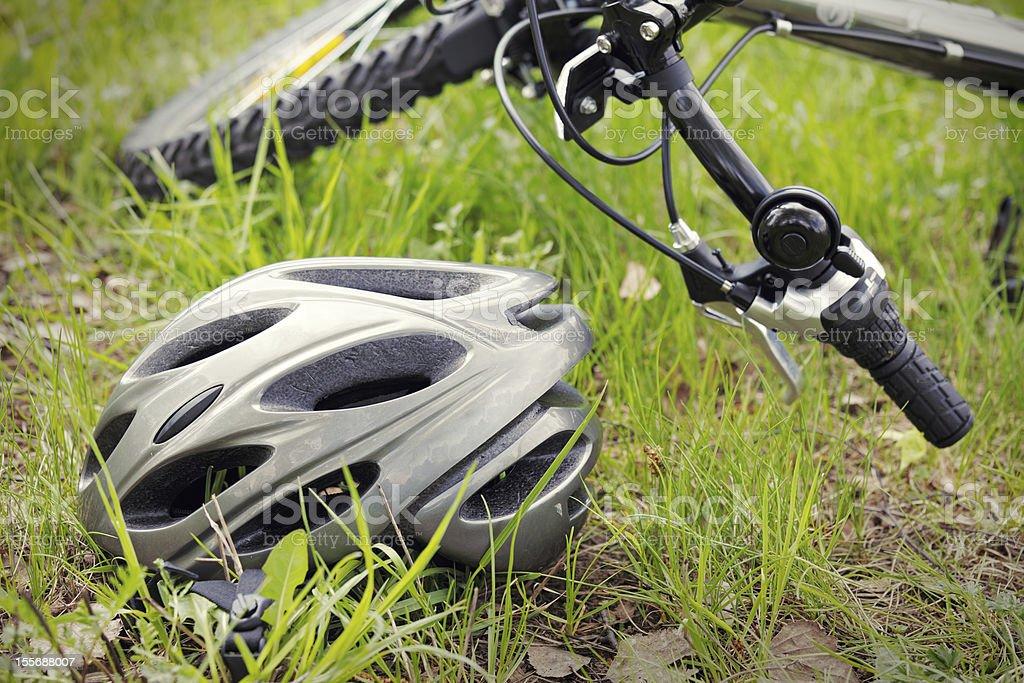 Helmet and bike on grass stock photo
