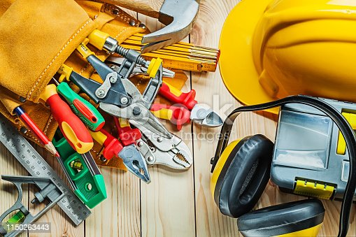 helmet construction tools in tool belt and toolbox with earphones on wood boards