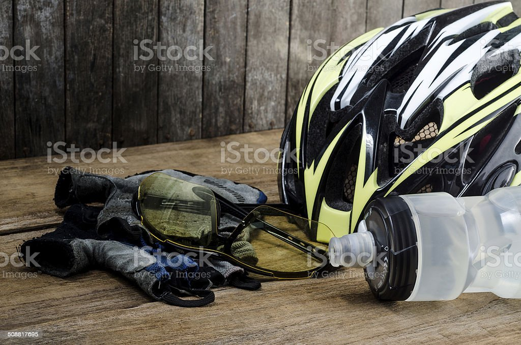Helmet, gloves and water bottle - bicycle accessories on Wood stock photo