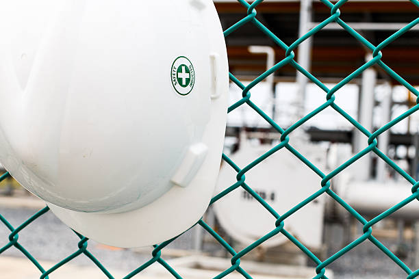 Helmet hang on green net fence stock photo