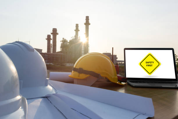 Helmet on table in a power plant industry. Energy power station area with sky, sunset. Safety in factory Concept. symbol safety first on laptop stock photo