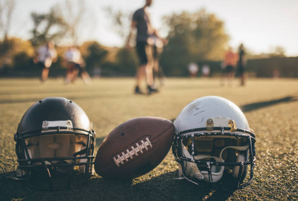 NFL helmets and ball on grass on training American football helmets and ball on the playing field. ncaa college football stock pictures, royalty-free photos & images