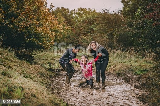 Women are taking part in a charity obstacle course. One woman is stuck in a muddy ditch and the other two are trying to help her get out. They are laughing to hard to be able to lift her.