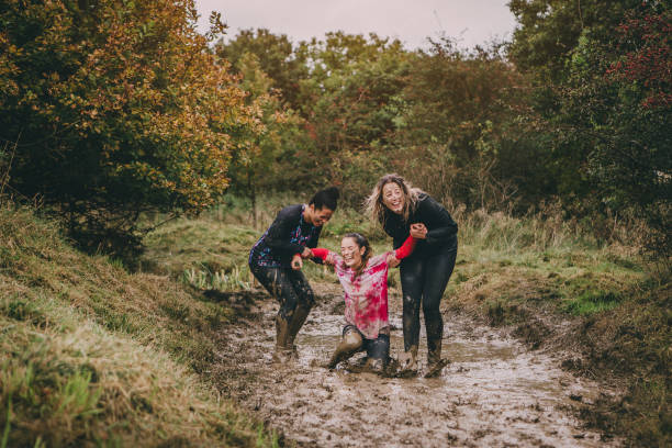 Help A Girl Out Here! Women are taking part in a charity obstacle course. One woman is stuck in a muddy ditch and the other two are trying to help her get out. They are laughing to hard to be able to lift her. mud run stock pictures, royalty-free photos & images