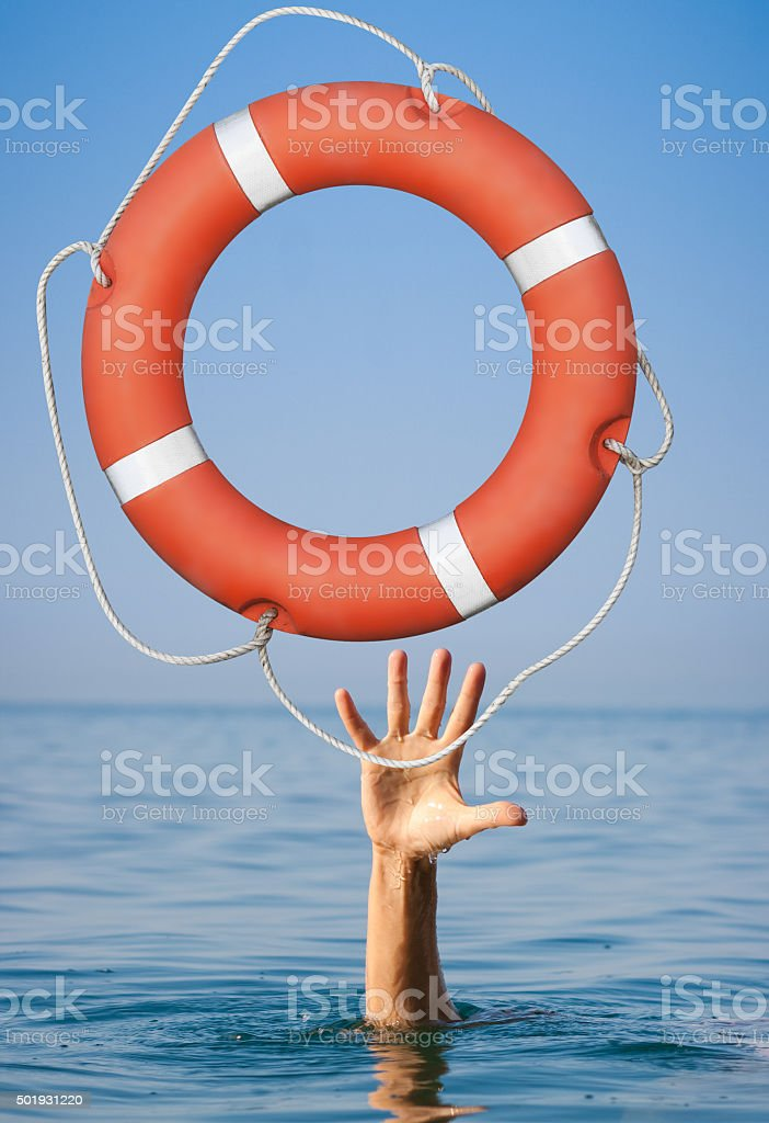 Help concept. Lifebuoy for drowning man's hand in open stock photo