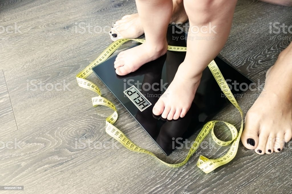 Help fat or obese child with toddler on weight scale, supervised by a parent stock photo