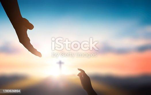 istock Help hand of God reaching over blurred cross on sunrise  background Help hand of God reaching over blurred cross on sunrise  background 1283636894