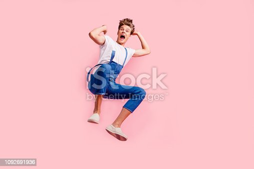 istock Help me I am falling! Full length body size studio photo portrait of trend cool overjoyed with toothy smile guy raise hands up isolated pastel background copyspace 1092691936