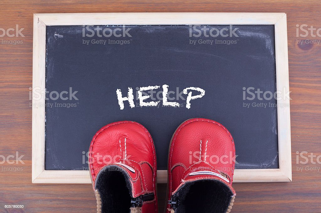 Help message and kid shoes on on chalkboard stock photo