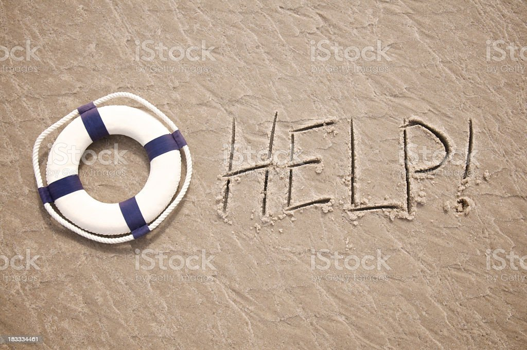 Help Message Written in Sand with Lifesaver stock photo