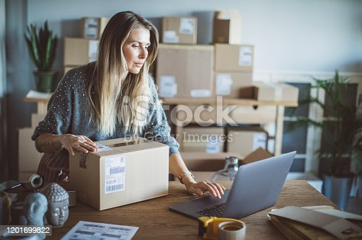 Working woman at online shop. She wearing casual clothing and checking on laptop address of customer and package information