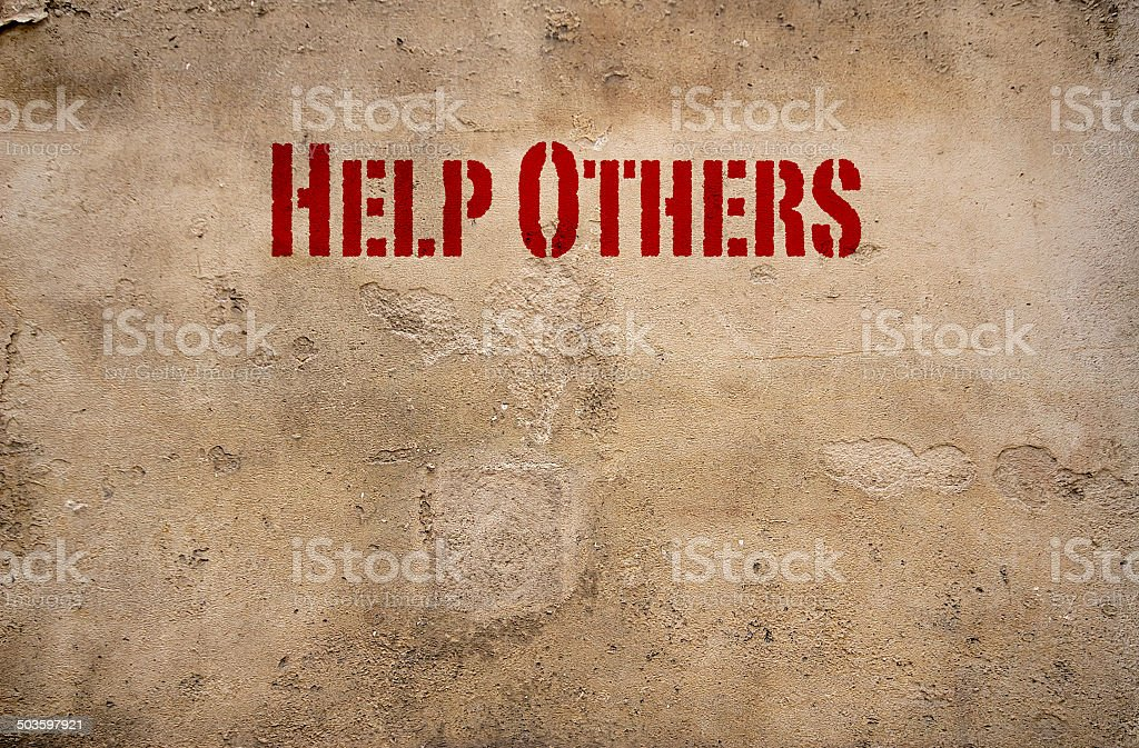 Help others sign on a concrete wall stock photo