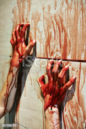 A cropped shot of a woman's bloody hands on a bathroom wall