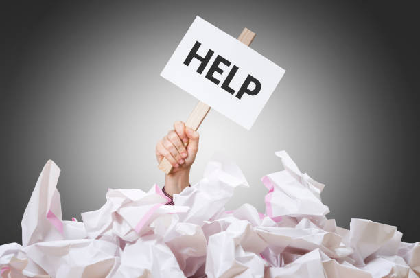 Help placard Help placard in hand with crumpled paper pile. bureaucracy stock pictures, royalty-free photos & images