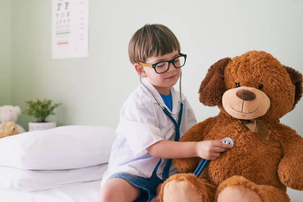 Help them find their aspirations Shot of a little boy pretending to be a doctor while examining his teddybear teddy bear stock pictures, royalty-free photos & images