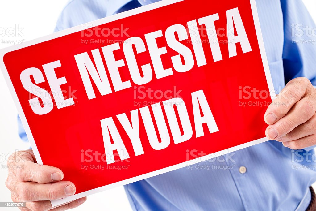 Help Wanted sign in Spanish held by man. royalty-free stock photo